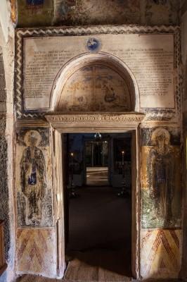 Εντυπωσιακή πύλη εισόδου στον ναό με επιγραφή στο μαρμάρινο υπέρθυρο και τοιχογραφίες στις παραστάδες.