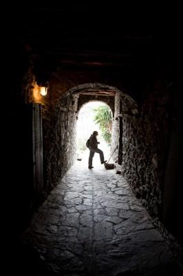 Με μήκος 50 περίπου μέτρων και παρά το ηλεκτρικό φως, το καμαροσκέπαστο σοκάκι είναι μισοσκότεινο, στο Αγάπι.
