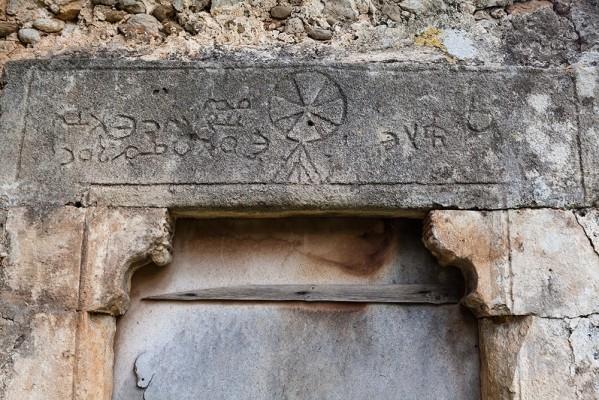 Εγχάρακτο πέτρινο υπέρθυρο, τοποθετημένο ανάποδα πάνω από τις παραστάδες της πόρτας