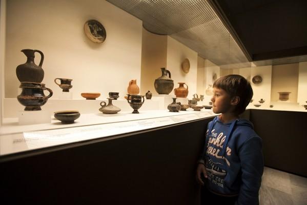 Ο μικρός Ραδάμανθυς εντυπωσιασμένος παρατηρεί τα εκθέματα μιας προθήκης