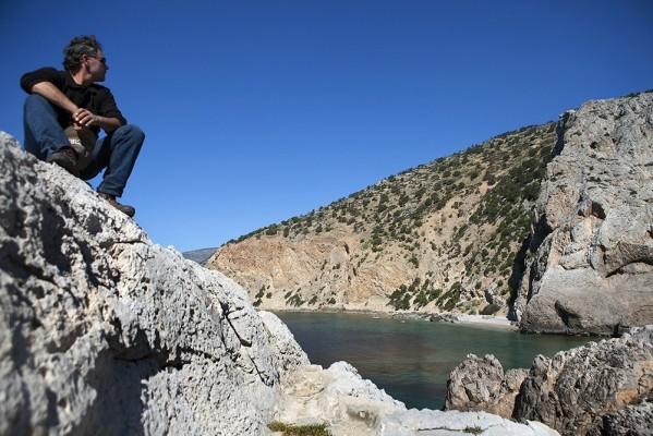 Σκαρφαλωμένος στον βράχο, ο Θανάσης Οικονόμου αγναντεύει τα βελούδινα νερά.