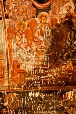 Αναρίθμητα απαράδεκτα χαράγματα ευσεβών προσκυνητών έχουν δημιουργήσει αληθινό Ληξιαρχείο τοίχου στις αγιογραφίες του βυζαντινού ναού των Αγίων Ταξιαρχών.