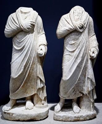 Δύο σχεδόν όμοια και μικρότερα του φυσικού μεγέθους ακέφαλα αγάλματα φιλοσόφων, που βρέθηκαν στο χώρο της Εξέδρας Αγαλμάτων στο συγκρότημα του Σεβαστείου 1ος αι. μ.Χ.