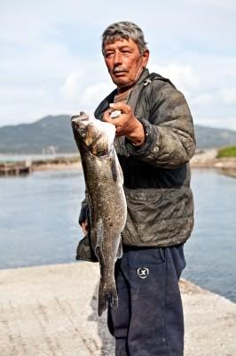 Ο Αντρέας Ίσερης επιδεικνύει ένα υπέροχο τρίκιλο λαυράκι, που αλιεύτηκε στη λίμνη.