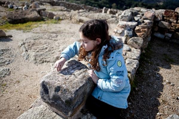 Η μικρή Αθηνά παίζει το αρχαίο παιχνίδι Πέντε γραμμαί.